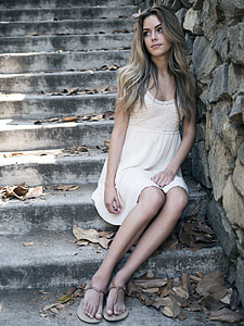 woman wearing white sleeveless dress sitting on concrete step