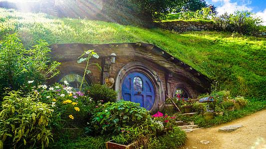 brown wooden underground house under green grass