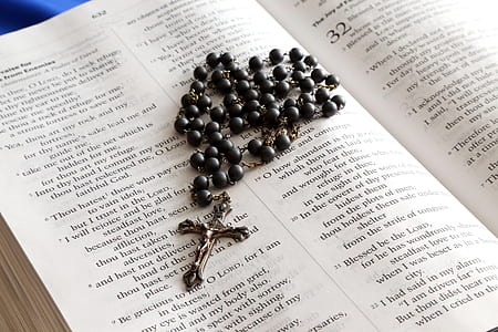 black and silver-colored rosary on bible