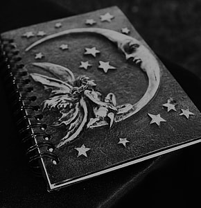 black and gray notebook with embossed crescent moon and fairy design