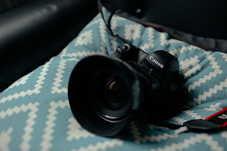 black Canon bridge camera on teal textile