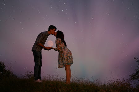 couple kissing with moon and stars in the background