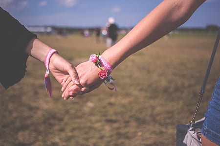 two person holding hands standing on grass field