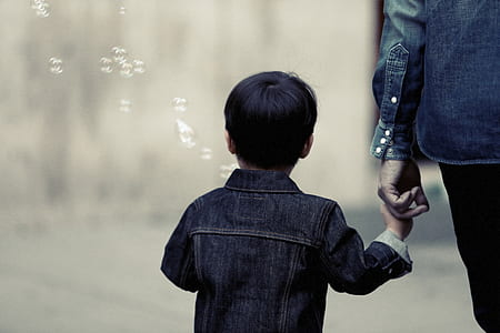 boy in denim jacket holding person's hand with bubbles in background