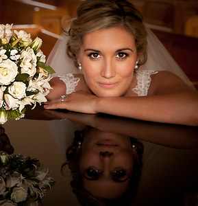 close up photography of bride with hand on black surface with bouquet of white roses