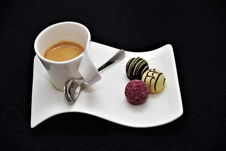 white ceramic teacup with coffee and pastries on top of ceramic dish