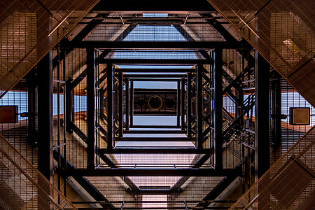 low angle photography of black and brown metal scaffolding frames during daytime