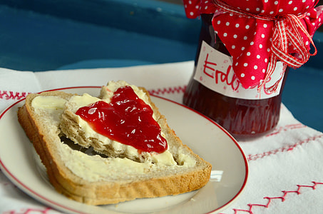 cream bread with strawberry jam on plate