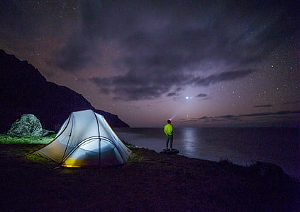 man standing near body of water near lighted dome tent at night