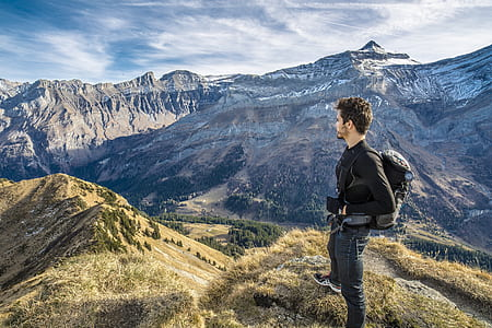 man wearin black jacket standing on a green mountain