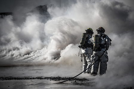 two man in fire suit on smoke