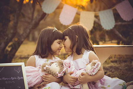 twin sisters holding pink ragdolls during sunset