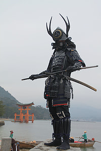 person Yushimitsu costume standing on gray concrete wall
