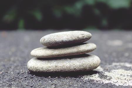 three gray stone piled on gray sand