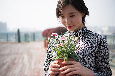 woman holding pink flowers during daytime