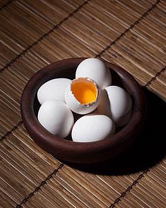 cracked egg on five eggs inside bowl