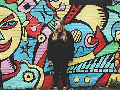 woman wearing black shirt leaning back on graffiti wall