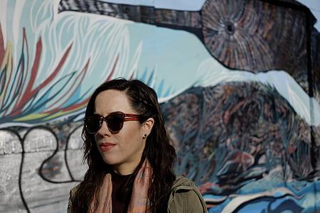 woman wearing black sunglasses beside the mural painting