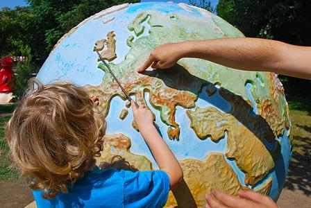 boy wearing blue t-shirt learning globe during daytime
