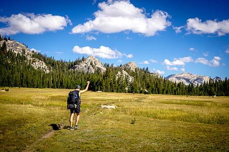 man wearing black backpack walking on green grass during daytime