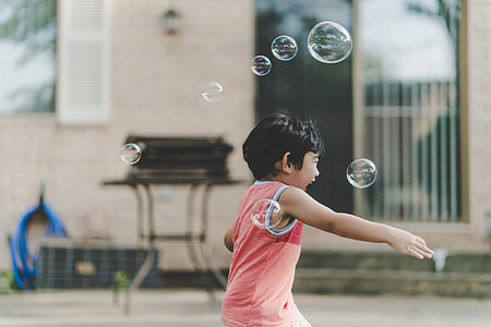 photo of a boy having fun playing with bubbles