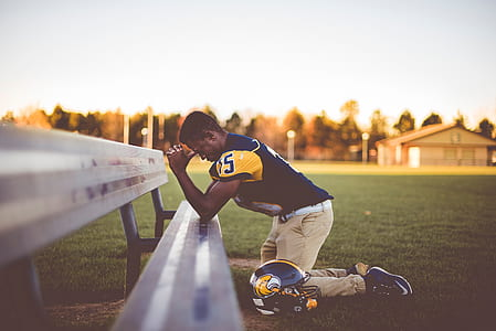 football player praying on bench