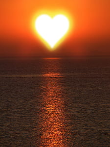 heart-shaped sun over body or water