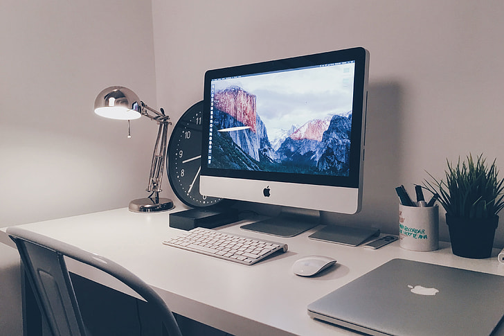 iMac computer and laptop on white office desk table