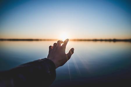 man reaching sun rays on body of water