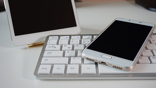 silver Samsung Android smartphone on top of Apple brand keyboard