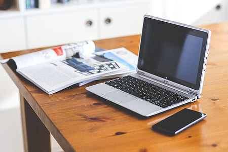 gray Acer laptop and black smartphone on brown wooden table