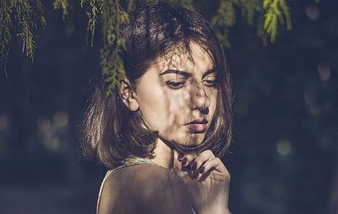 woman's face under green grass