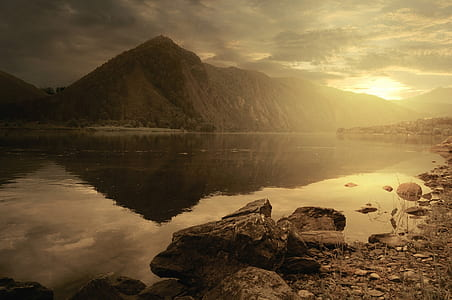 photo of calm water of lake near mountain during golden hour