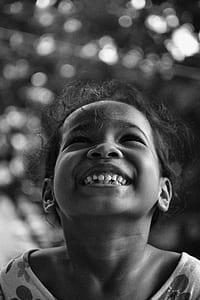 greyscale photo of smiling girl wearing top