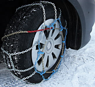 gray vehicle wheel with tire and chains