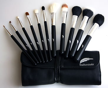 black-and-gray makeup brush set on white wooden board