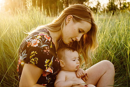 woman carrying baby sitting on grass field