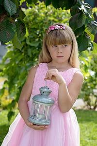 girl in dress holding lantern beside tree