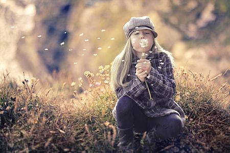 girl blowing dandelions
