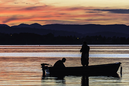 silhouette of two person on jon boat under orange sky