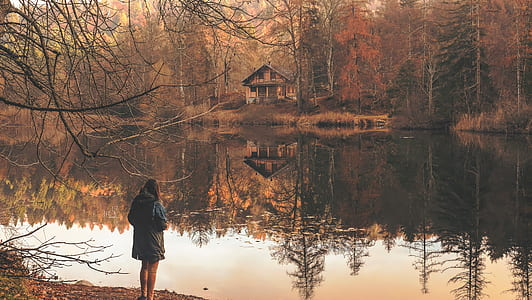 woman wearing jacket standing near body of water photography