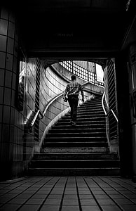 grayscale photo of man carrying books while walking on stairs at a subway station