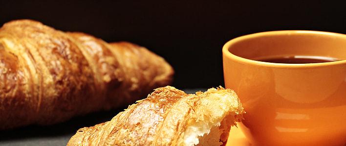 baked croissant near brown ceramic mug