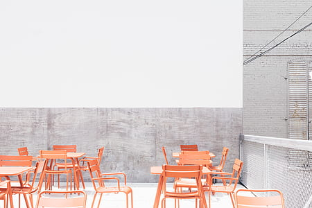 orange metal chairs and tables on rooftop during daytime
