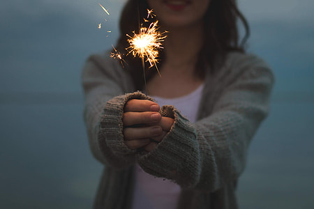 shallow focus photography of woman in gray knitted cardigan holding fireworks