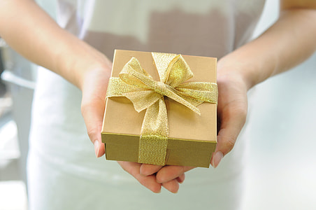 person holding gold box with ribbon