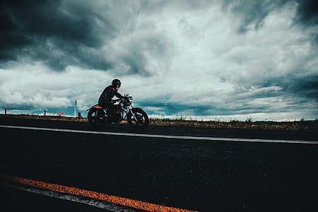 Moody shot of a man on the road riding a motorbike