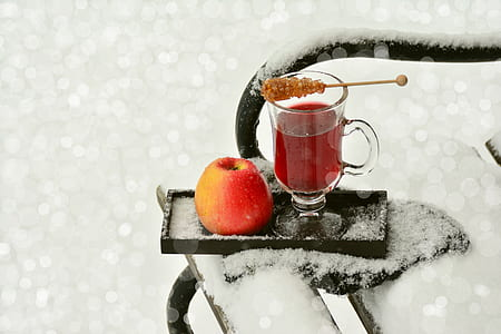 clear glass footed mug and red apple on black wooden ice covered tray