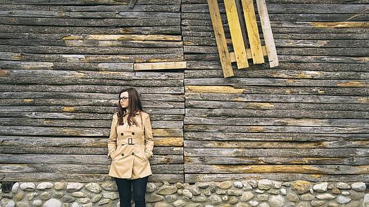 woman in beige coat leaning on brown wall