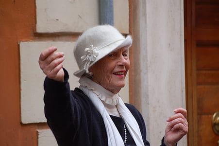 woman wearing white cloche hat and black long-sleeved top